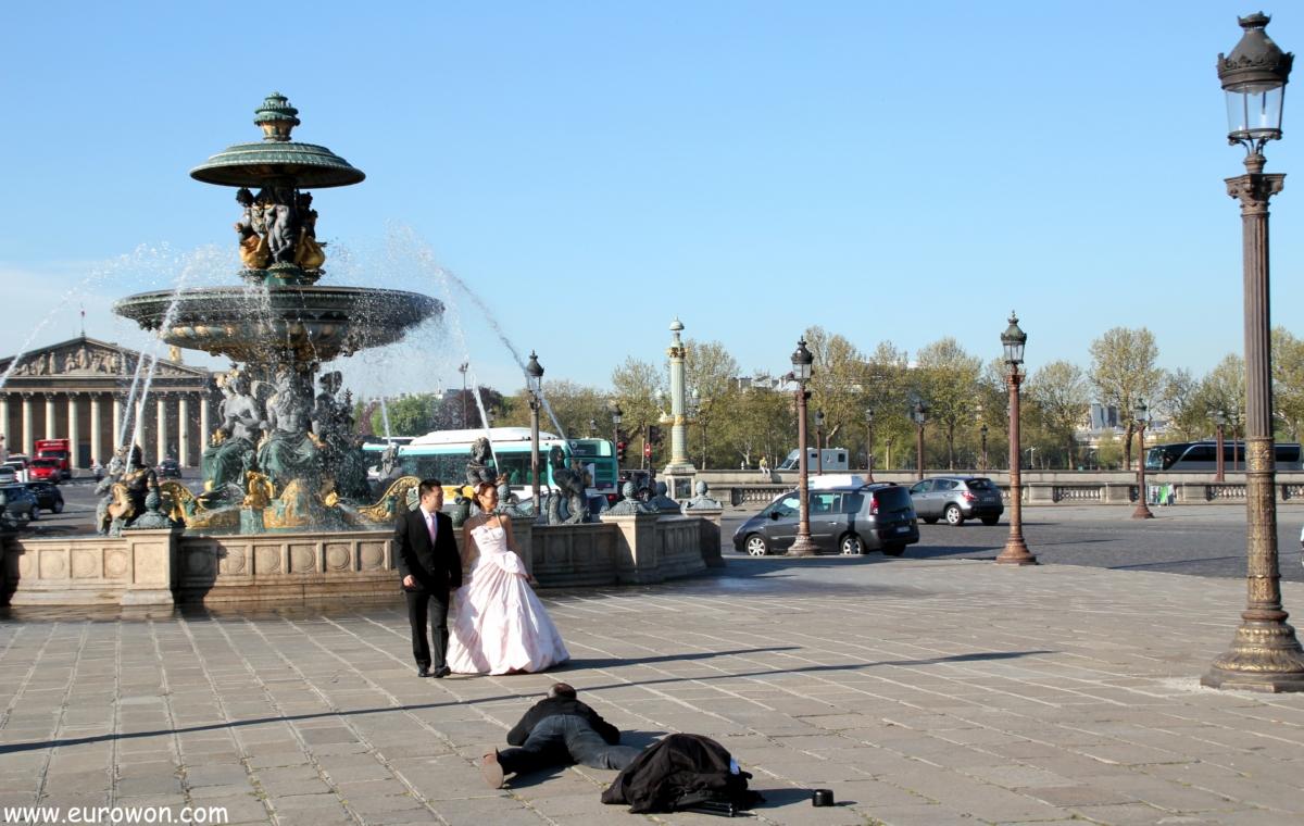 Pareja de recién casados asiáticos tomándose fotos en la plaza de la Concordia
