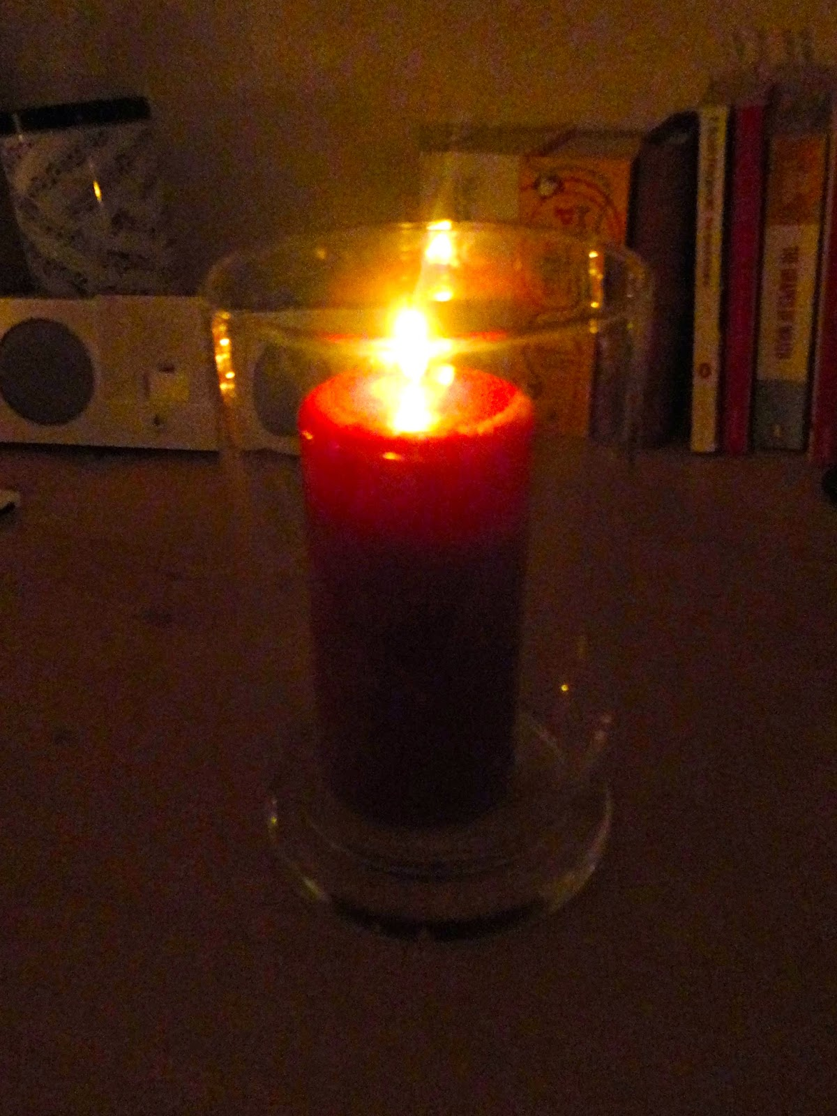 Red scented pillar candle lit in glass hurricane jar