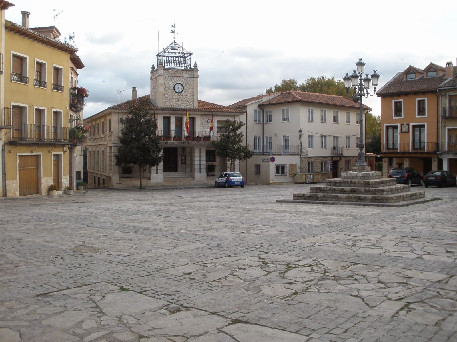 Plaza Mayor de Brihuega, cuadrada, con el ayuntamiento al fondo y rodeada de comercios de productos de la zona.