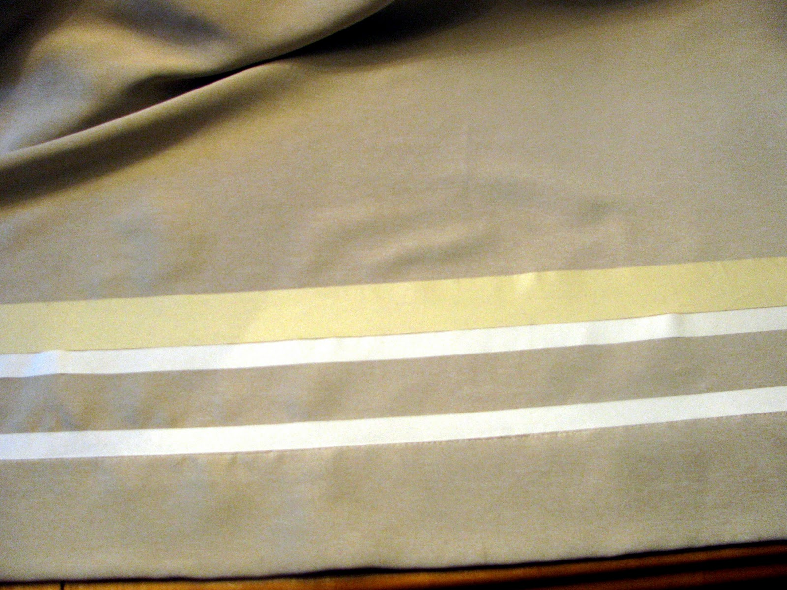 remodelaholic no sew curtain panels inspired by ballard designs once the tape is removed and placed above the third strip of no sew the final stripe can be ironed down i chose four stripes using 1 black satiny ribbon
