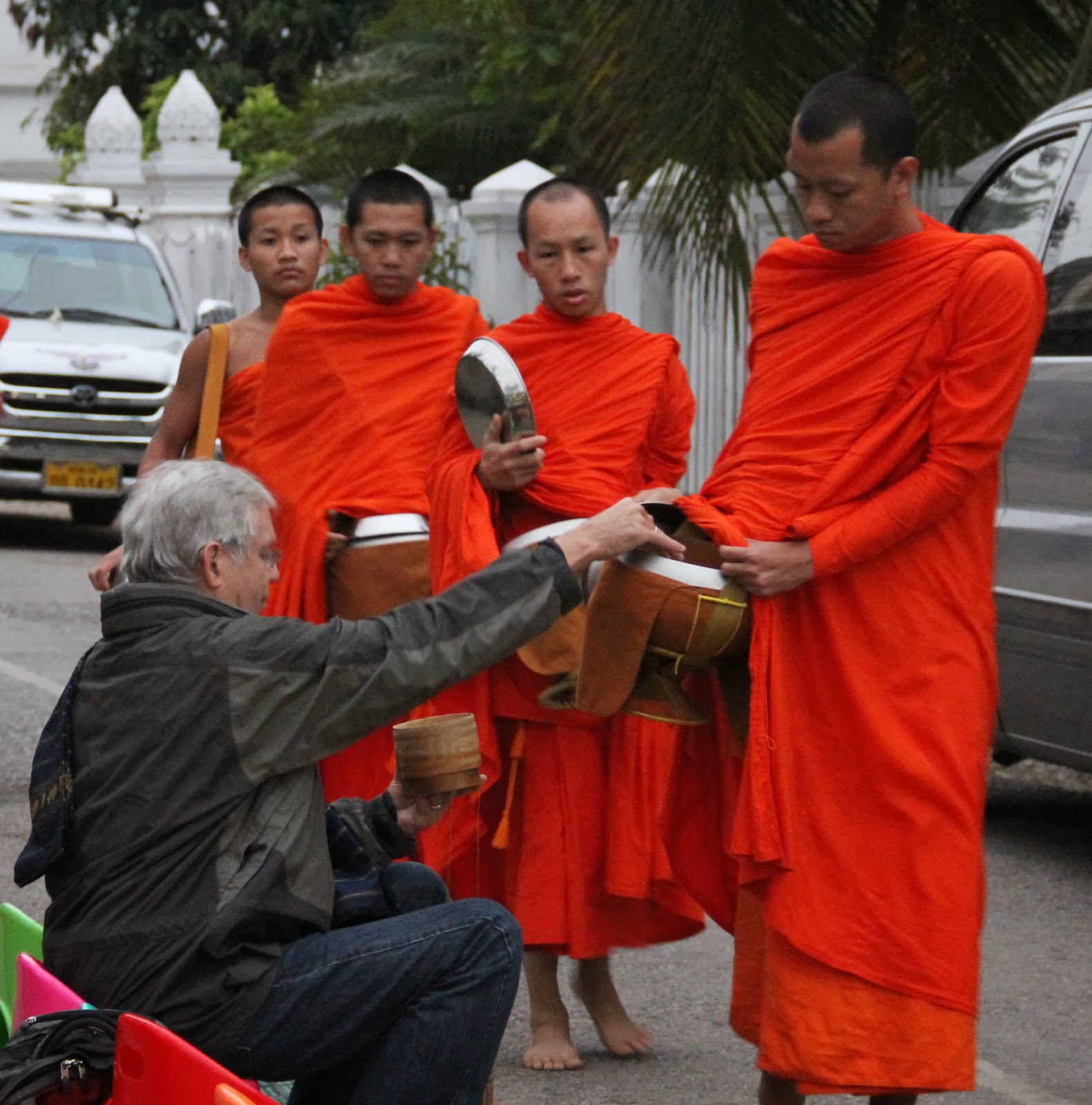 Ted giving alms of sticky rice to young monks at dawn in Luang Prabang.