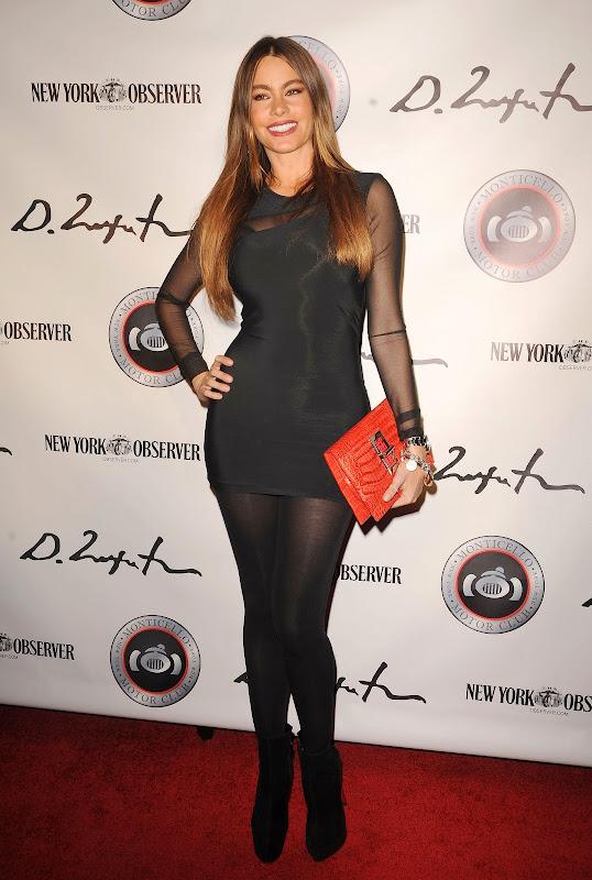 Sofia Vergara wearing a black mini dress and black stocikings