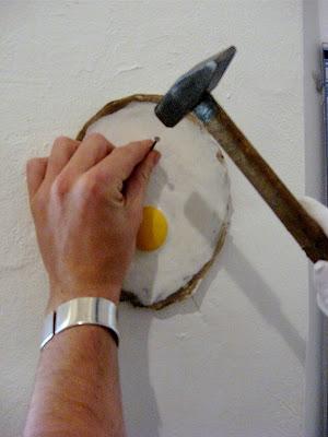 Zwei Männerhände nageln ein Spiegelei an die Wand