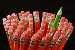 Group of red pencils with one green one raised