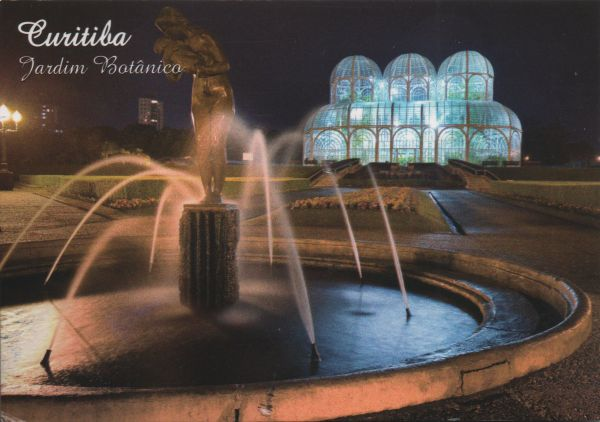 night view of a fountain with illuminated glasshouse in the abckground
