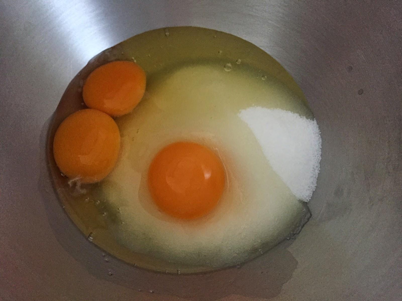 Magdalenas rellenas de mermelada, batiendo azúcar y huevos.