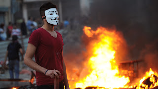 Anonymous #OpTurkey, Government websites hacked in support of Protests - Demostrator wears Guy Fawkes mask as protesters clash with Turkish riot policemen against the demolition of Taksim Gezi Park, Istanbul