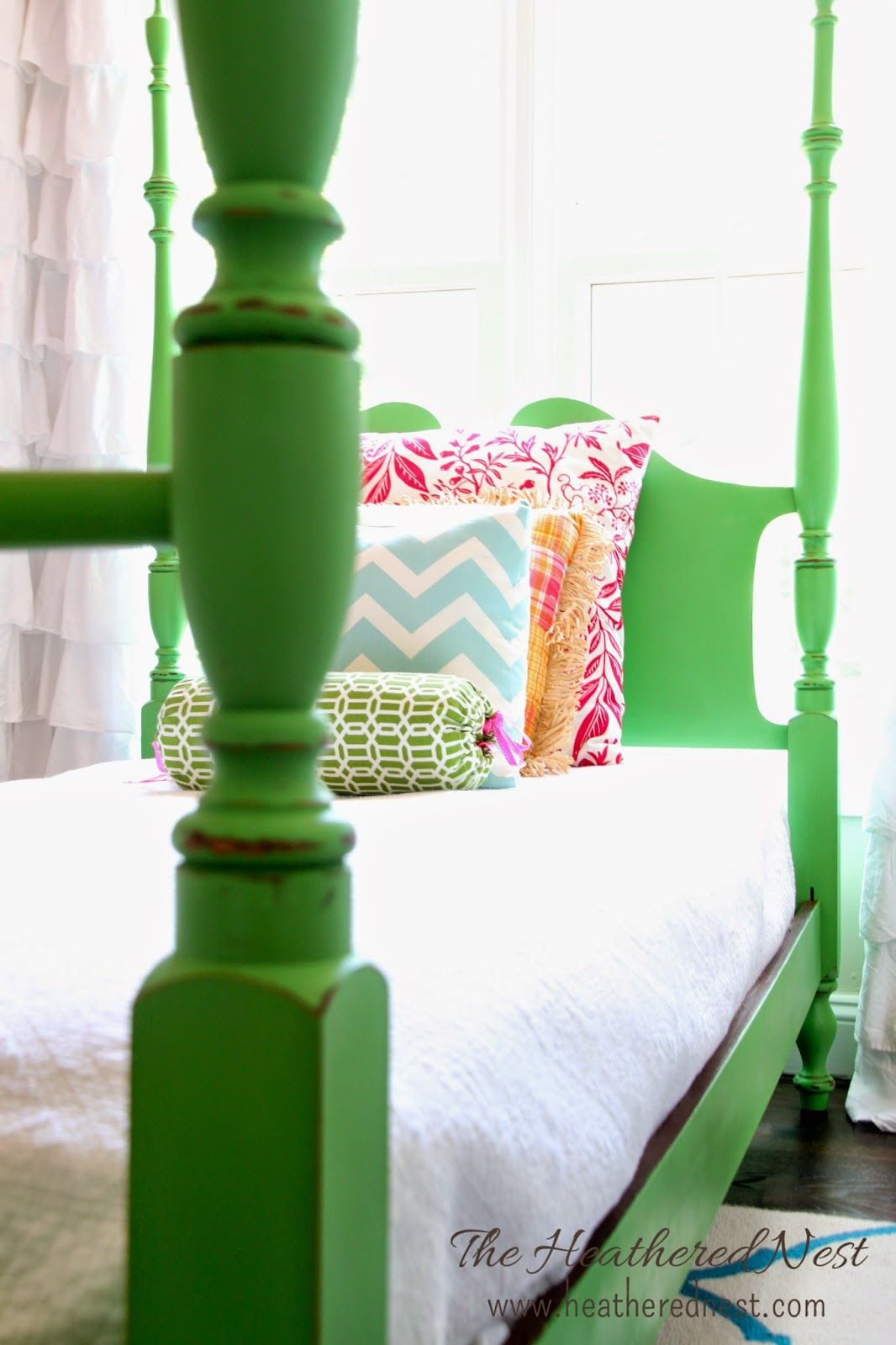 close up of Annie Sloan Antibes Green poster bed from Heathered Nest with bolster pillow and other throw pillows