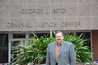 Ian Lovestock poses in front of Criminal Justice Center entrances.