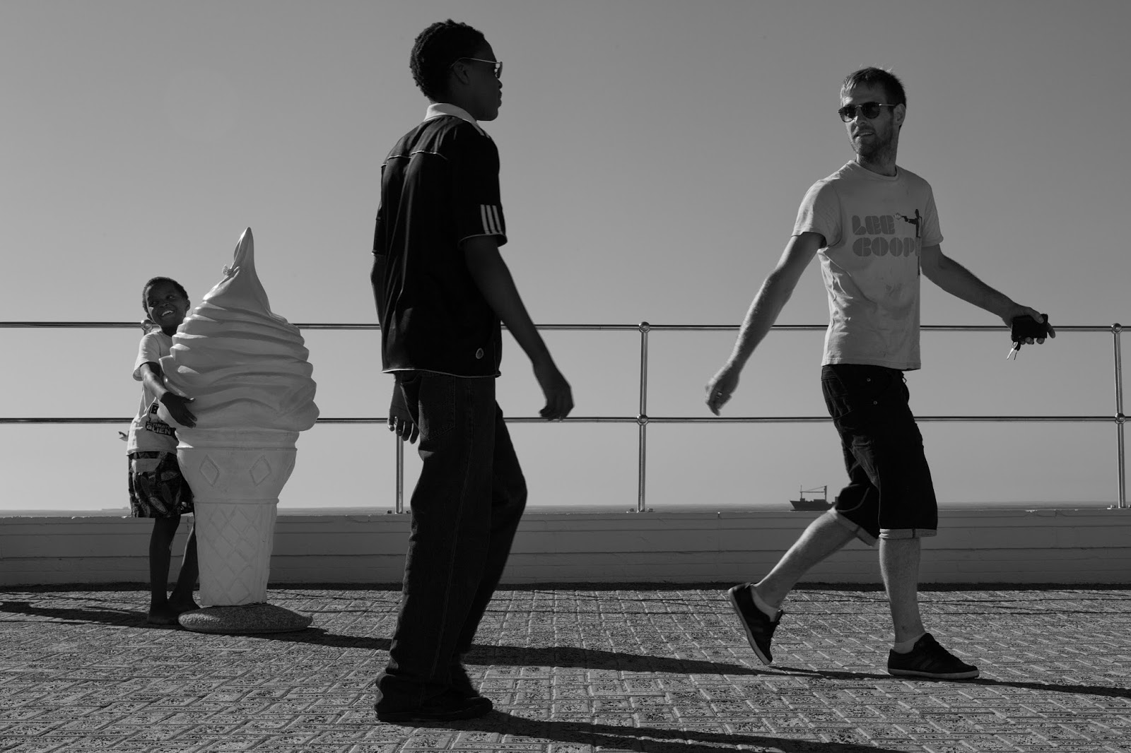 A boy hugs a giant ice cream while two young men have a passing interaction
