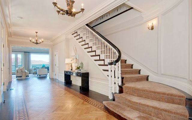 foyer with a herringbone inlay and a view into the living room and ocean. A grand staircase with carpeting and two chandeliers