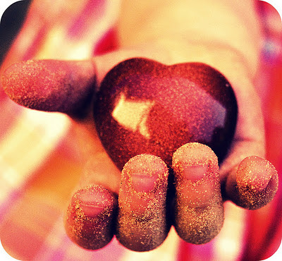 child's outstretched hand holding sparkly red heart charm