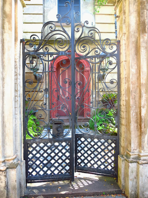 Scrolling wrought iron gate and an arched red door with checkered marble path in Charleston, South Carolina