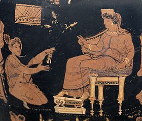 Demeter, enthroned and extending her hand in a benediction toward the kneeling Metaneira, who offers the triune wheat.