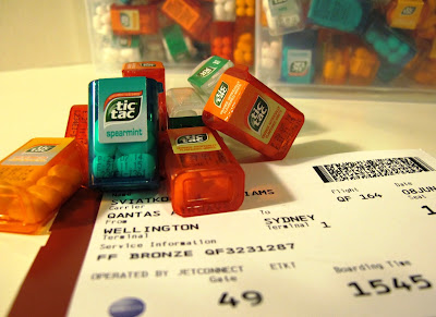 Airplane boarding pass with a pile of Tic Tac minis piled on it.