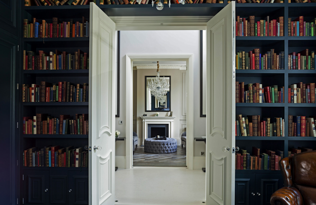 Blue library in a suburban London home with built in bookshelves and leather club chairs