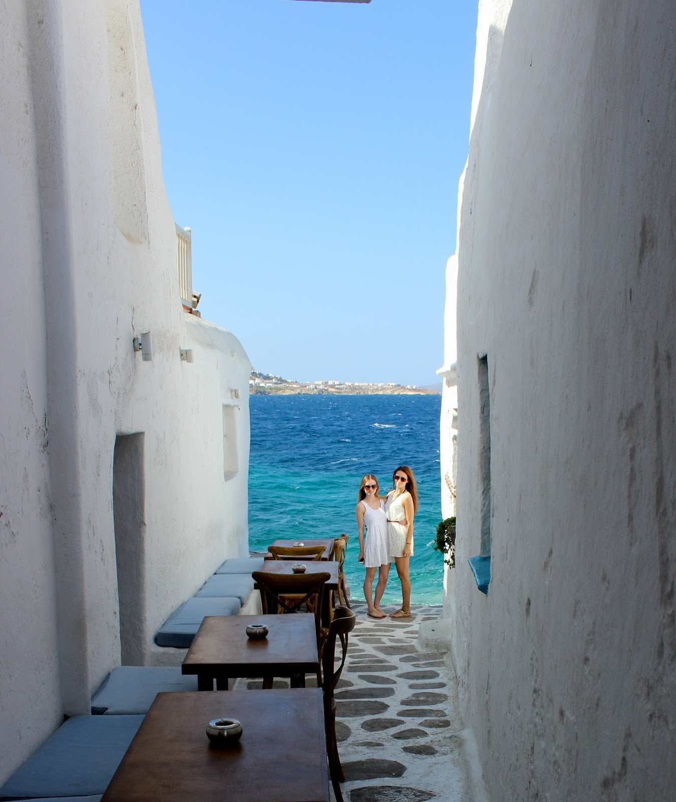 Girls with mykonos beauty surroundings, white blue and cobbled streets.
