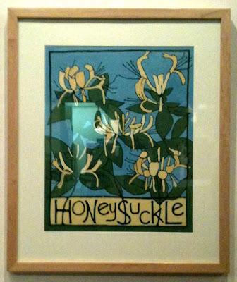 painting by Megan Moore of yellow honeysuckle blooms with a blue background and the plant name lettered in black across the bottom