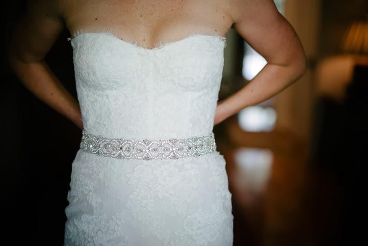 detail shot of bride putting on her wedding dress sash