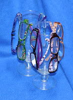six pairs of reader glasses with hurricane drinking glasses