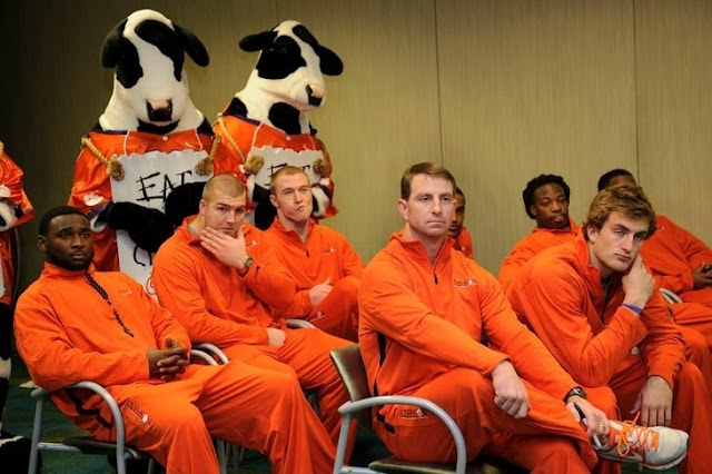 Clemson HC Dabo Swinney and his team look like convicts in all-orange team warm-up unis.