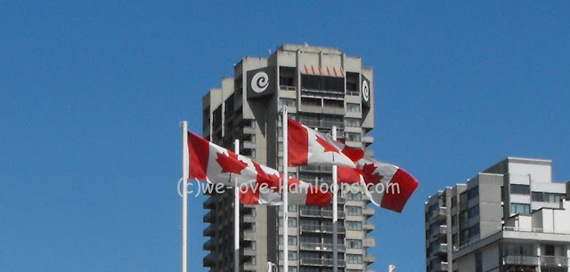 Several flags of Canada flying in the wind in Vancouver