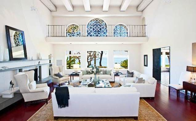 living room with hard wood floor, white dueling sofas and armchairs, a