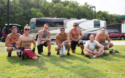 A shirtless Tim McGraw poses for the camera after a final tour workout with his band and crew