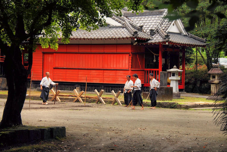Four men practicing martial art with swords