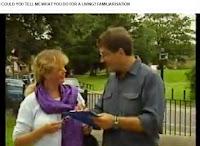 entrevistador en la calle con una mujer vestida con un fular morado