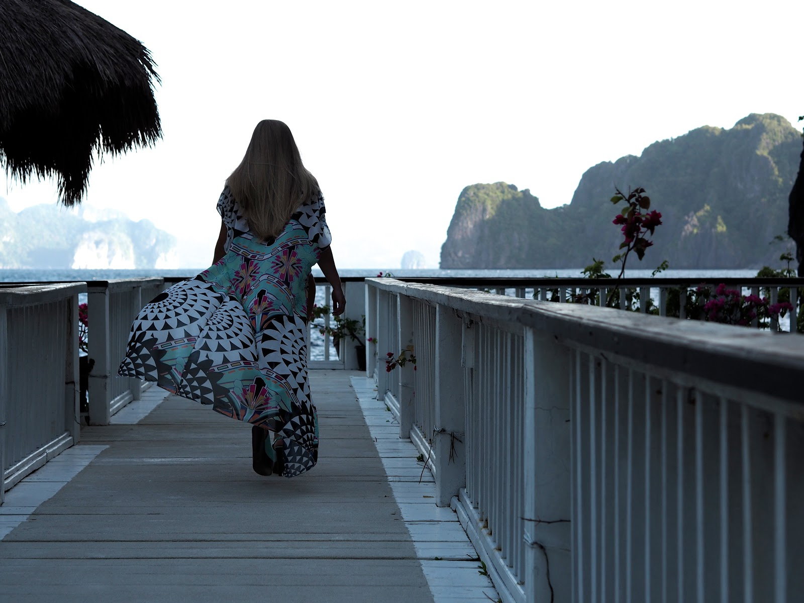 blonde girl walking down jetty wearing long colourful kimono