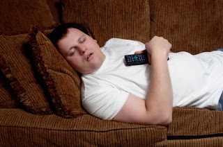 Guy Laying on the sofa or couch sleeping with a remote in his hand