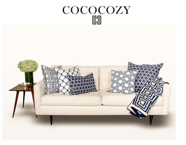 Assortment of navy pillows and throw on sofa with green hydrangea flower arrangement.