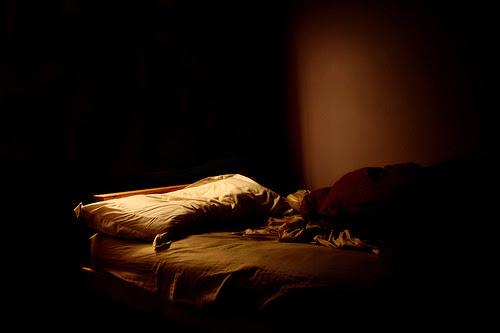 Imagen de una cama sola, de ambiente triste y a medio iluminar.