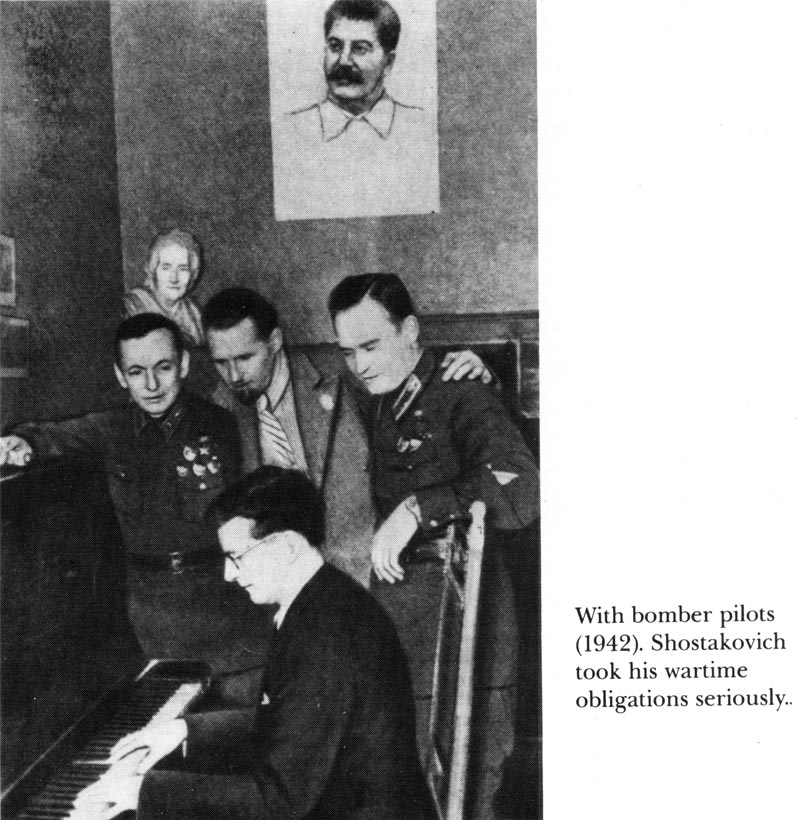 a picture of Stalin looks over the shoulder of Shostakovich as he plays piano.