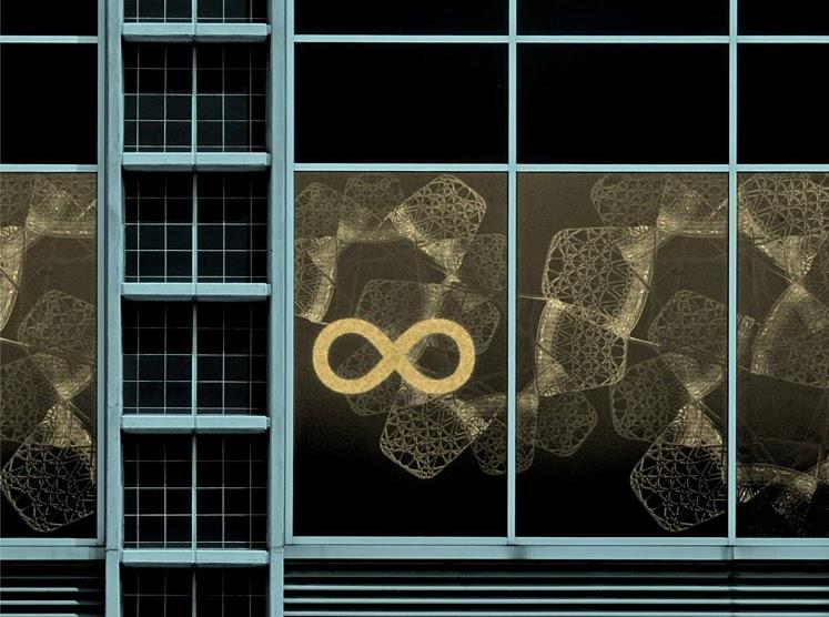 """Parede em vidro tapado com papel com grafismos da loja """"Área"""". Sobre a esquerda uma janela vertical."""
