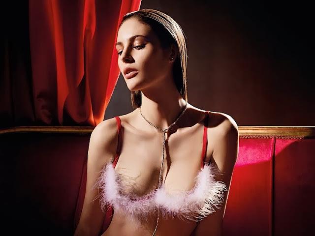 lingerie verdissima pour noël soutient gorge en satin rouge et boa de plumes blanches très sexy. Femme brune cheveux attaché nue, glamour sur canapé