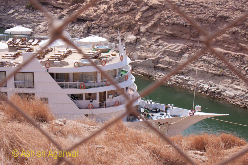 View of cruise ship on the waters of Lake Nasser, through a barred fence at Abu Simbel in Egypt