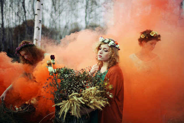 witches, a beautiful forest fantasy, flower crowns, flower garlands, girls holding woven baskets of dried flowers in a cloud of orange smoke, smoke bomb photography, smoke bomb, colored smoke, smoke grenade, fantasy, Levitsky