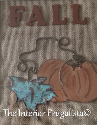 Attaching green twine and wooden letters to tin pumpkin art