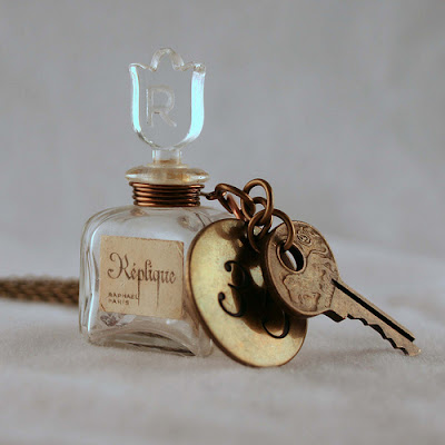 Tiny glass perfume bottle necklace with brass disk engraved number 52 and an antique master key with engraved lion on it.