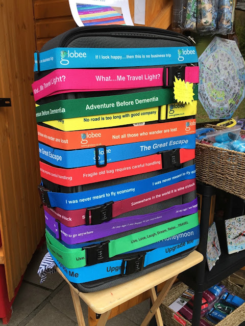 A suitcase covered in brightly coloured luggage straps