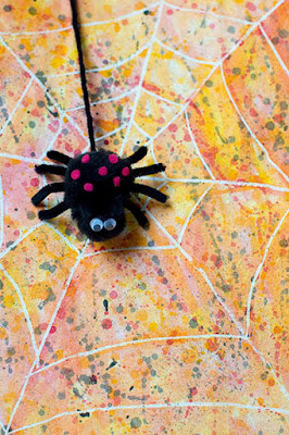 Cute black pom pom spider with pink felt spots on a beautiful orange red yellow and black watercolor background