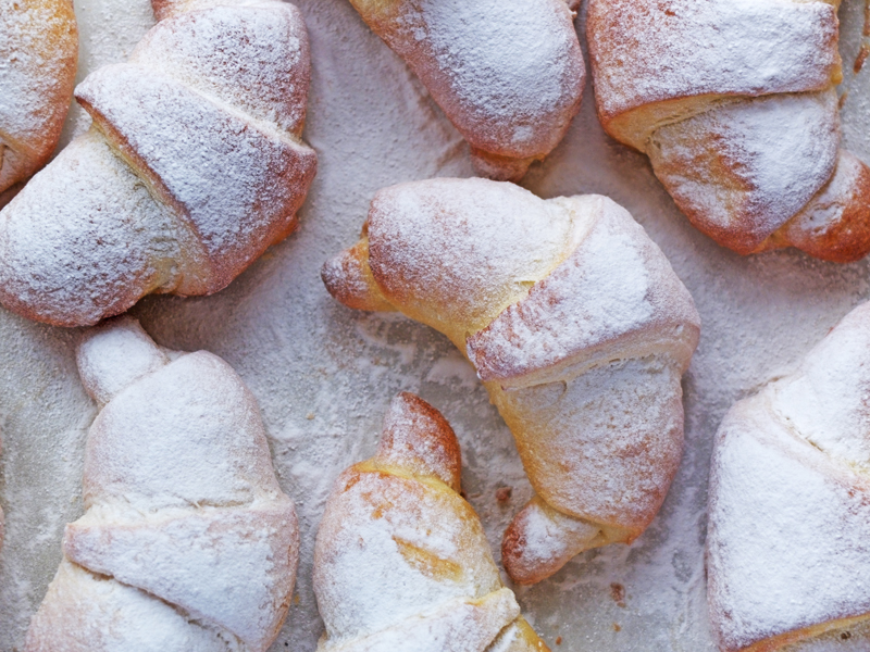 Close up of Nutella crescents dusted with icing sugar on a tray.