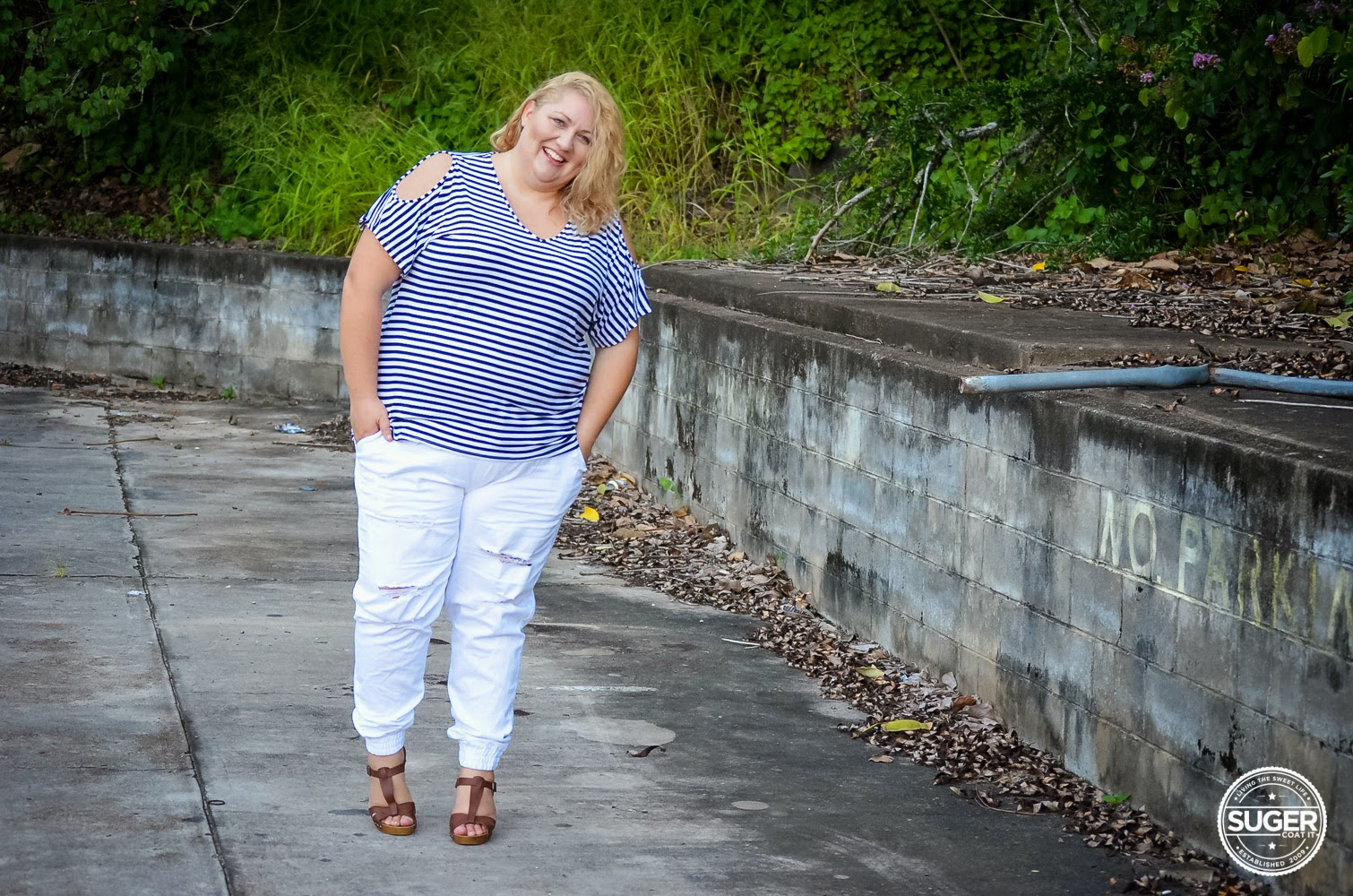 Melissa from Suger Coat It blog wearing blue and white striped top and white pants
