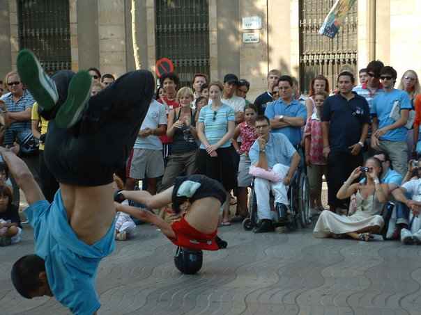 Man in wheelchair watches breakdancers.
