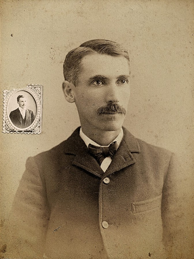 Studio portrait, with short hair going gray at the temples, a thin neck, large eyes. Suit is tight and straight.