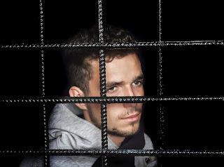 A prisoner behind bars.