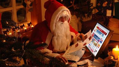 Santa Claus revisa la lista de regalos en su pc para Navidad
