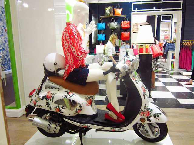 mannequin sitting on a floral scooter